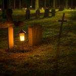 A lantern next to a tombstone